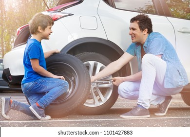 Happy father and son changing wheels on car