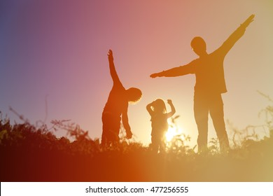 happy father with son and daughter play at sunset