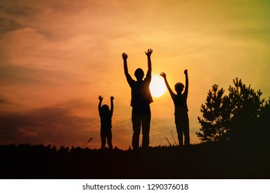 happy father with son and daughter silhouettes play in sunset