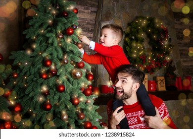 Happy Father and son enjoying decorating Christmas tree with Christmas balls and light garland preparing for celebrating winter holidays: Merry Christmas Eve and Happy New Year 2019. Family concept.
