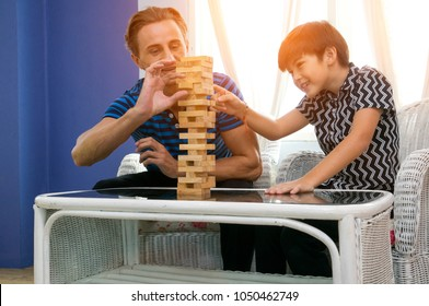 Happy father with son , excited with wooden block game at home.