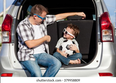 Happy father and son getting ready for road trip on a sunny day.  Concept of friendly family.