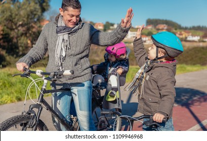Happy father and son giving five by the success in the learn to ride a bicycles in the city on a sunny winter day.  Family leisure outdoors concept.