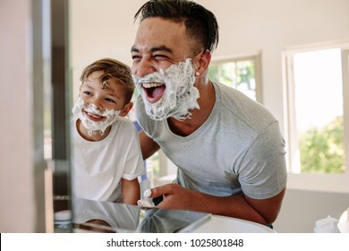 Happy father and son having fun while shaving in bathroom. Young man and little boy with shaving foam on their faces looking into the bathroom mirror and laughing.