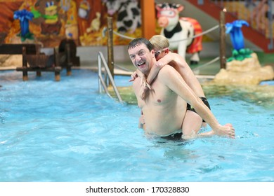 Happy father with son having fun in the swimming pool