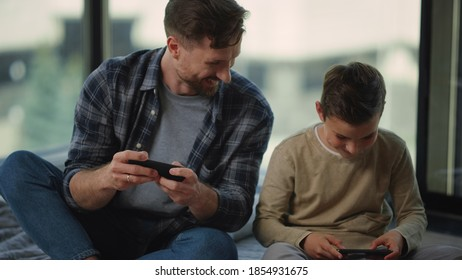 Happy father and son having fun with mobile phones at home. Funny dad and boy gaming on smartphones indoors. Curious parent and kid playing mobile games on phones inside.