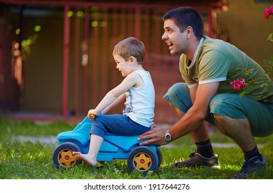 happy father and son having fun, playing with bobby car on the home backyard at sunny summer day