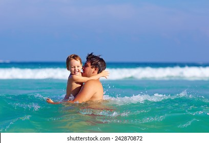 happy father and son having fun in water waves