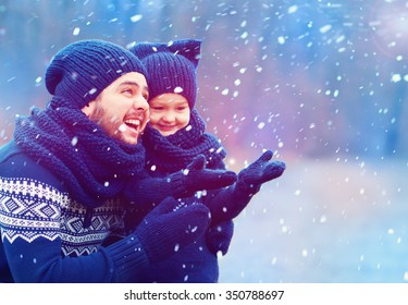 happy father and son having fun under winter snow