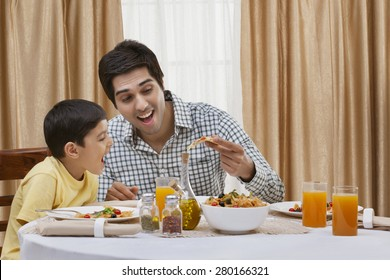 Happy father and son having pizza at restaurant