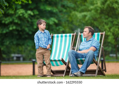 Happy father and son having rest in city park on beautiful summer day