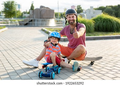 Happy father and son in helmets play in the Park with a robot car that is controlled by a glove while sitting on skateboards.
