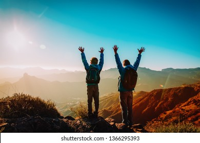 Happy father and son hiking at sunset mountains