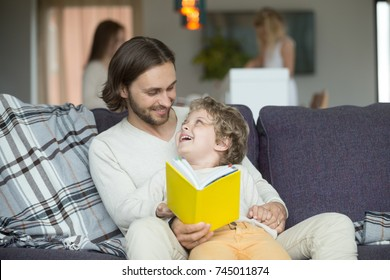 Happy father and son holding yellow book sitting on sofa, dad embracing little boy reading fairy tale to smiling kid on couch, parents with children having fun at home, family leisure activities
