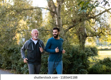 Happy father and son jogging together outdoors in park.