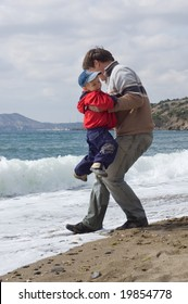 happy father and son jump in waves on the beach
