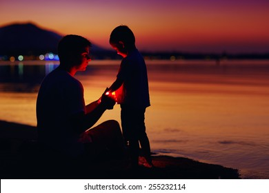 happy father and son with lantern at sunset beach