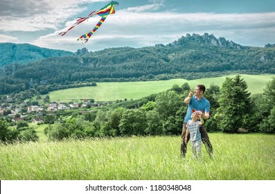Happy father and son launch a kite to blue sky on the field in summer sunny day.