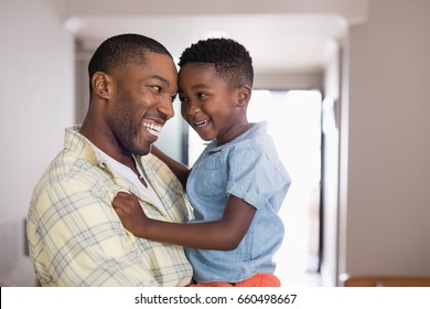 Happy father and son looking at each other in living room