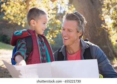 Happy father and son looking a map in the forest