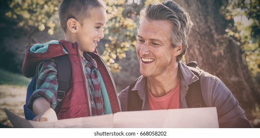 Happy father and son looking map in forest