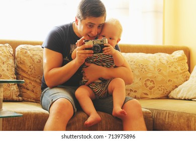 Happy father and son are looking at an old camera in the background of sunlight. Special work photo for vintage style.