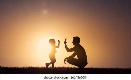 Happy father and son moment. Father giving his son a hight five outdoors in the park. Father's Day, fatherhood concept.