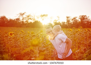 Happy father with son on back walking on a green field of blooming sunflowers at sunset.