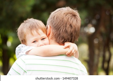 Happy father and son outdoors.  Child hugging daddy.