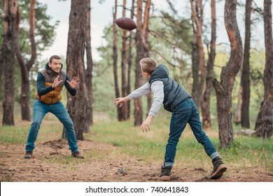 happy father and son playing football together in forest