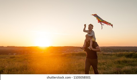 Happy father and son playing with a kite while running on meadow, sunset. Travel and vacation in summer. Freedom