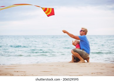 Happy father and son playing with kite at the beach at sunset