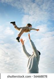 glücklicher Vater und Sohn, der auf Himmelshintergrund spielt