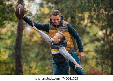 happy father and son playing with rugby ball in forest