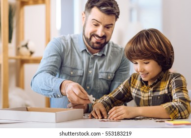 Happy father and son playing table game