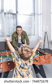happy father and son playing table football together at home
