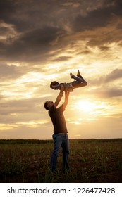Happy father and son playing together at sunset time, Father throwing his son in the air