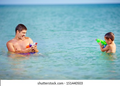 happy father and son playing with water pistols