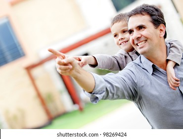 Happy father and son pointing away - outdoors