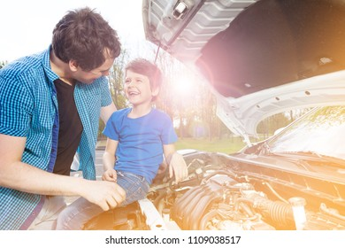 Happy father and son repairing car outside
