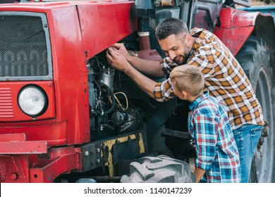 happy father and son repairing tractor engine together