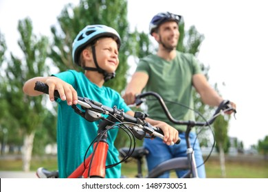 Happy father and son riding bicycles outdoors