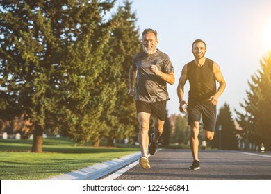 The happy father and a son running on a park road