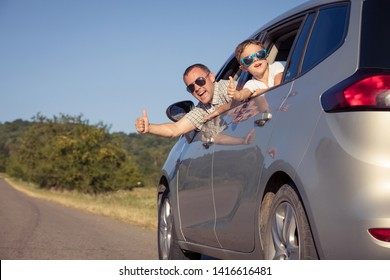 Happy father and son sitting in the car at the day time. They look out the window. People having fun outdoors. Concept of the family is ready for travel.