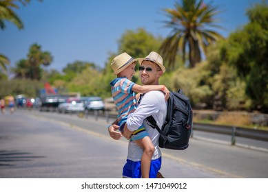 Happy father and son in sunhats spending time together on summer vacations. Son is on father'hands hugging him.