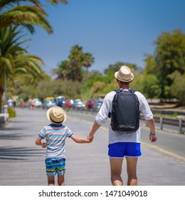 Happy father and son in sunhats spending time together on summer vacations. They are holding hands. Back view.