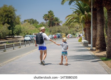 Happy father and son in sunhats walking together on summer vacations. They are holding hands. Back view.
