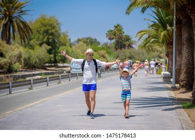 Happy father and son in sunhats walking together on summer vacations. They are holding hands.