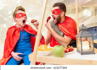 Happy father and son in superhero costumes eating strawberries in blanket fort