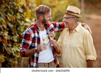 Happy father and son tasting wine in vineyard